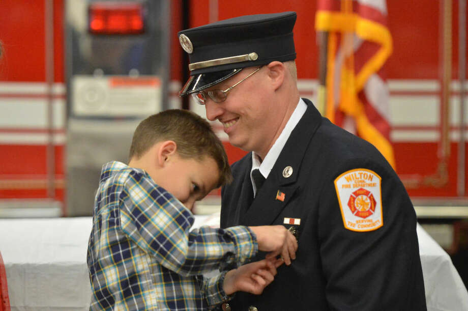 Firefighter Bill Wilson has his badge pinned on him by his 7-year-old son Jackson as he is promoted to lieutenant during a ceremony at Wilton Fire Headquarters that promoted Bill Sampson to Lieutenant and Firefighters James Blanchfield and Brian Elliott to captain.