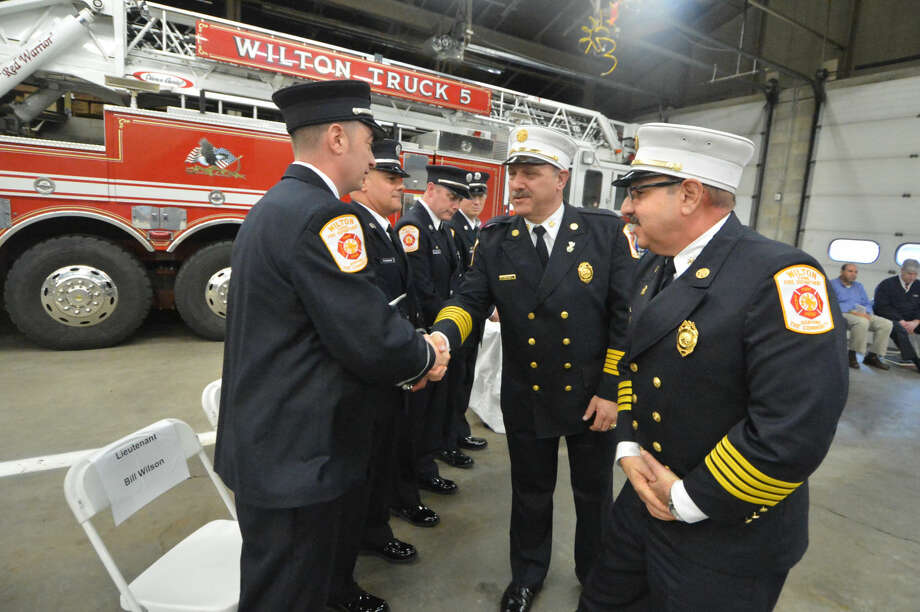 Wilton Fire Chief Ronald Kanterman and Deputy Chief Mark Amatrudo pass out new shields for helmets during a ceremony at Wilton Fire Headquarters that promoted Bill Sampson and Bill Wilson to lieutenant and Firefighters James Blanchfield and Brian Elliott to captain.