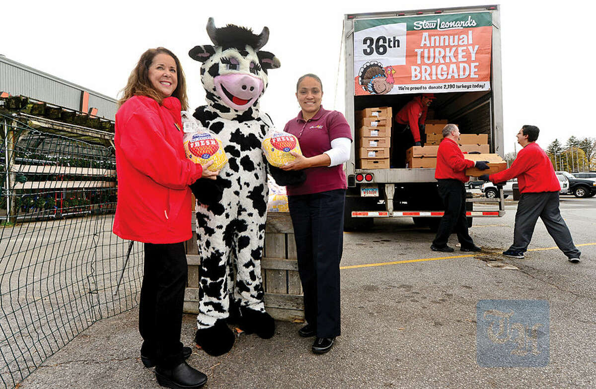 Hour photo / Erik Trautmann Jill Leonard Tavella and Wow the Cow hand Lt. Carmen Colon of the Salvation Army frozen turkeys as Stew Leonard's continues its long-standing tradition of giving back to the communities it serves with it's 36th Annual