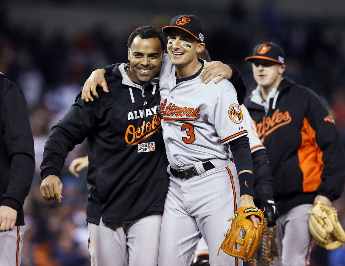 Baltimore Orioles' Nelson Cruz and Ryan Flaherty (3) react after Baltimore defeated the Detroit Tigers, 2-1, in Game 3 of baseball's AL Division Series Sunday, Oct. 5, 2014, in Detroit. Baltimore won the series 3-0. (AP Photo/Paul Sancya)