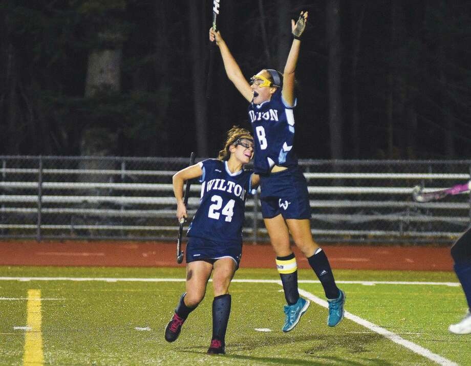 Hour photo/John Nash - Wilton's Jillian Mahon leaps into the air after scoring her team's fifth and final goal as fellow Warriors player Sophia Kaplan joins the celebration as Wilton beat Conard 5-0 in a CIAC Class L field hockey semifinal at Cheshire High School's Alumni Field on Tuesday.