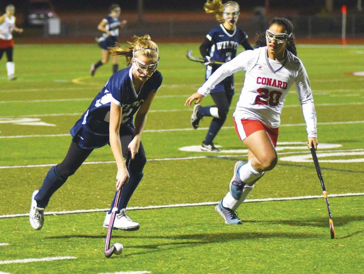 Hour photo/John Nash - Wilton's Maddie Duffy, left, pushes the ball up the field as Cheshire defender Zarin Ehsani chases during Tuesday's CIAC Class L semifinal at Cheshire High School's Alumni Field. Duffy scored two goals to lead Wilton to a 5-0 victory.