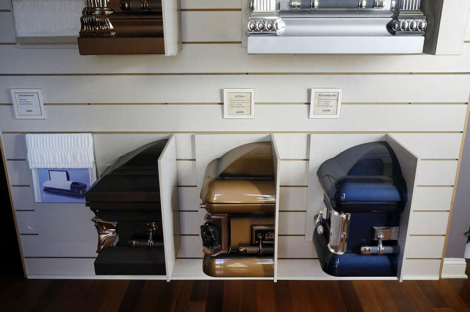 """In this Oct. 16, 2015 picture, options for caskets are on display in John Williams' funeral home Baltimore. In a city that routinely leads the country in violent crime, Baltimore's murder toll has proved harrowing, even to those in the death business. """"I try never, ever to get numb to this,"""" Williams said. """"But you have to shield yourself sometimes. Homicide is becoming my normal."""" (AP Photo/Patrick Semansky)"""