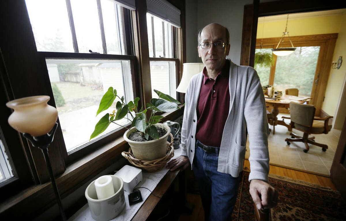 Former Iowa State University employee Dennis Smith, of Des Moines, Iowa, stands in his home, Tuesday, Nov. 17, 2015, in Des Moines, Iowa. Iowa State last year paid $650,000 to settle Smith's lawsuit alleging he was retaliated against by superiors, including subjected to a lengthy threat assessment investigation. The case is one example of the challenges facing university threat assessment teams, which were formed on many campuses after the 2007 Virginia Tech massacre. (AP Photo/Charlie Neibergall)