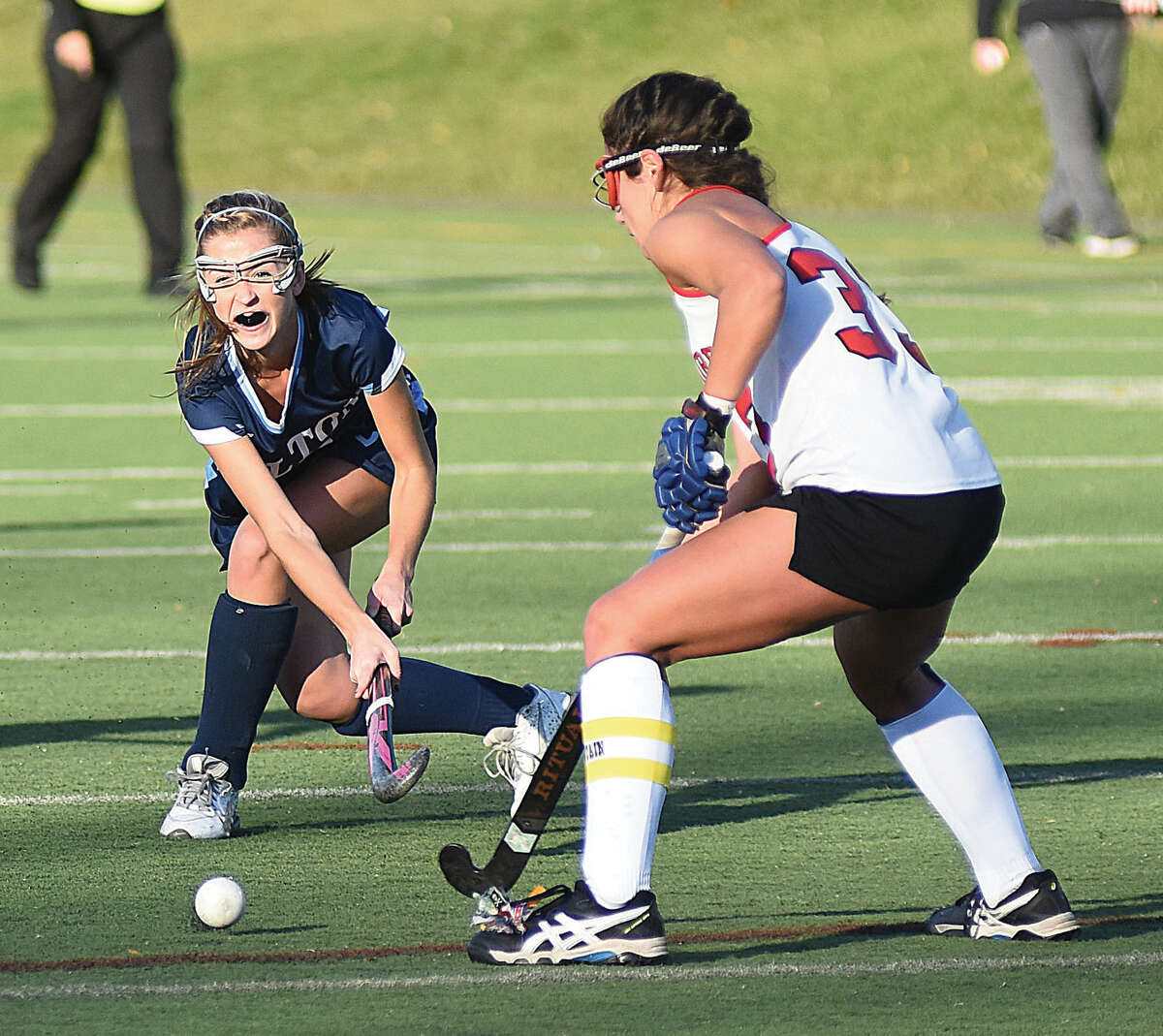 Hour photo/John Nash Wilton's Maddie Duffy, left, sends a pass by Cheshire defender Nicole Salamone during Saturday's CIACClass l championship game against Cheshire at Cottone Field in Wethersfield. Wilton won the game, 1-0, in overtime to give the Warriors their fourth state title in five years.