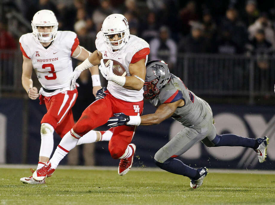 Connecticut safety Andrew Adams, right, tackles Houston running back Kenneth Farrow, center, during the third quarter of an NCAA college football game Saturday, Nov. 21, 2015, in East Hartford, Conn. (AP Photo/Stew Milne)