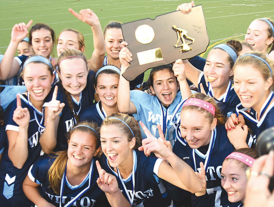 Hour photo/John Nash Members of the Wilton High field hockey team celebrate their fourth state championship in five seasons on Saturday at Cottone Field in Wethersfield. The Warriors defeated Cheshire 1-0 in overtime to take the state's big-school title.