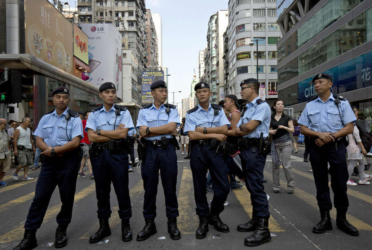 Police officers stand guard at a main road in the Mong Kok area in Hong Kong, Monday, Oct. 6, 2014. Student-led protests for democratic reforms in Hong Kong shrank Monday but a few hundred demonstrators remained camped out in the streets, vowing to keep up the pressure until the government responds to their demands. (AP Photo/Vincent Yu)