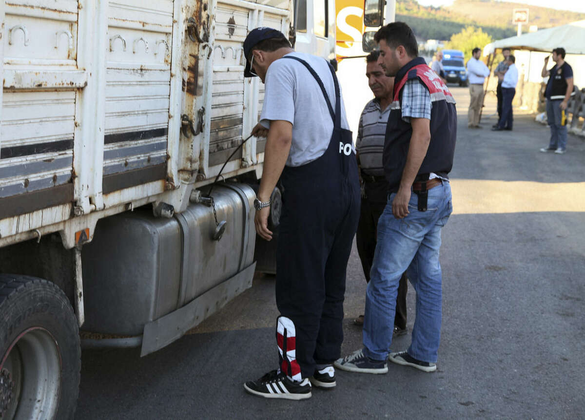 FILE - In this Saturday, Sept. 20, 2014 file photo, Turkish anti-smuggling experts check a truck on a road near Hacipasa, Hatay, Turkey. At the peak of Turkey's oil smuggling boom, the main transit point was a dusty hamlet called Hacipasa on the Orontes River that marks the border with Syria. Hacipasa has been a smuggling haven for decades, authorities and residents say. The fuel had come from oil wells in Iraq or Syria controlled by militants, including the Islamic State group, and was sold to middle men who smuggled it across the Turkish-Syrian border.(AP Photo/Burhan Ozbilici, File)