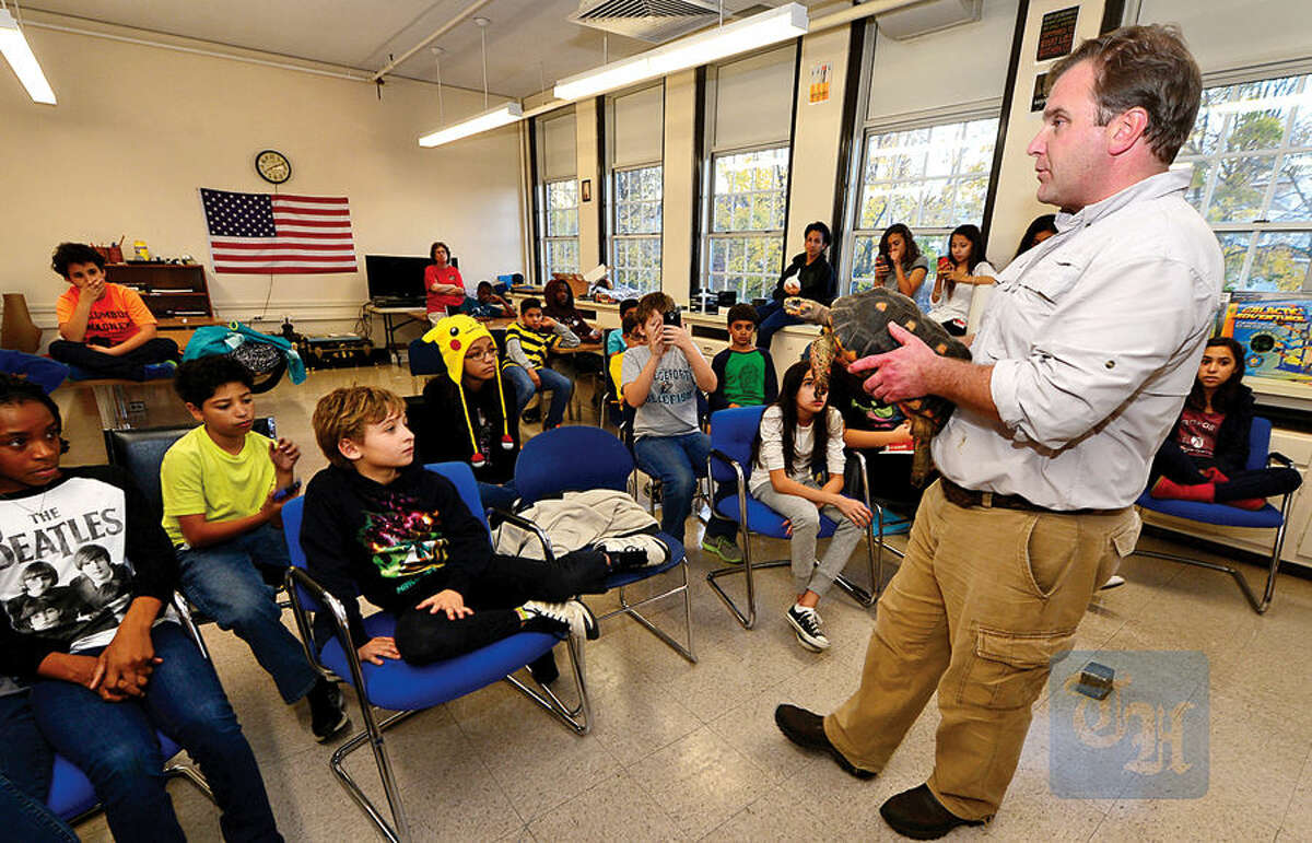 Hour photo / Erik Trautmann Chris Evers of Animal Embassy shows children in the Choices for Success after school program at the Ben Franklin Center a tortoise Friday. Choices for Success is a program of the Child Guidance Center and provides academic and enrichment activities for middle and high school students.