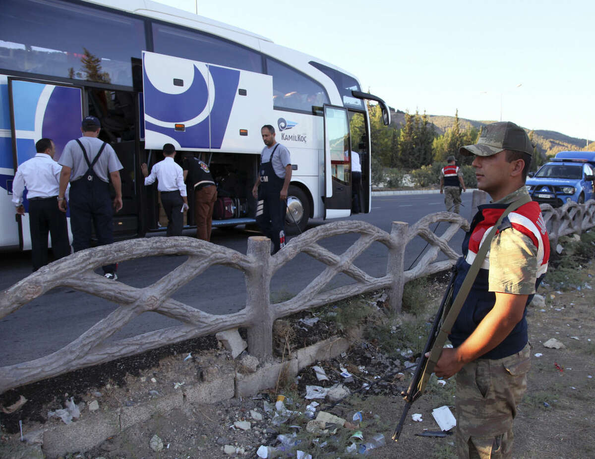 FILE - In this Saturday, Sept. 20, 2014 file photo, a Turkish soldier stands as anti-smuggling experts check a bus on a road near Hacipasa, Hatay, Turkey. At the peak of Turkey's oil smuggling boom, the main transit point was a dusty hamlet called Hacipasa on the Orontes River that marks the border with Syria. Hacipasa has been a smuggling haven for decades, authorities and residents say. The fuel had come from oil wells in Iraq or Syria controlled by militants, including the Islamic State group, and was sold to middle men who smuggled it across the Turkish-Syrian border. (AP Photo/Burhan Ozbilici, File)