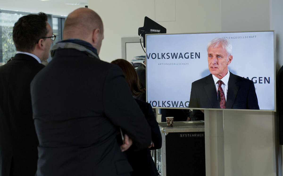 Matthias Mueller, Volkswagen AG CEO, is displayed on a TV screen, as he speaks during a news conference in Wolfsburg, Germany, Friday Nov. 20, 2015. Volkswagen CEO Michael Mueller says the company's board has decided to reduce capital expenditures by 1 billion euros (US $1.07 billion) in 2016 as it deals with the fallout of its emissions-rigging scandal. Mueller said Friday after a meeting of the board at company headquarters in Wolfsburg, German, that the cuts would bring capital expenditure down to 12 billion euros next year. (Julian Stratenschulte/dpa via AP)