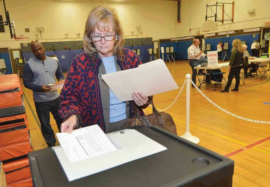 Hour Photo/Alex von Kleydorff Michele Kenaga casts her vote at Marvin Elementary School, District C1 during steady voting on Tuesday