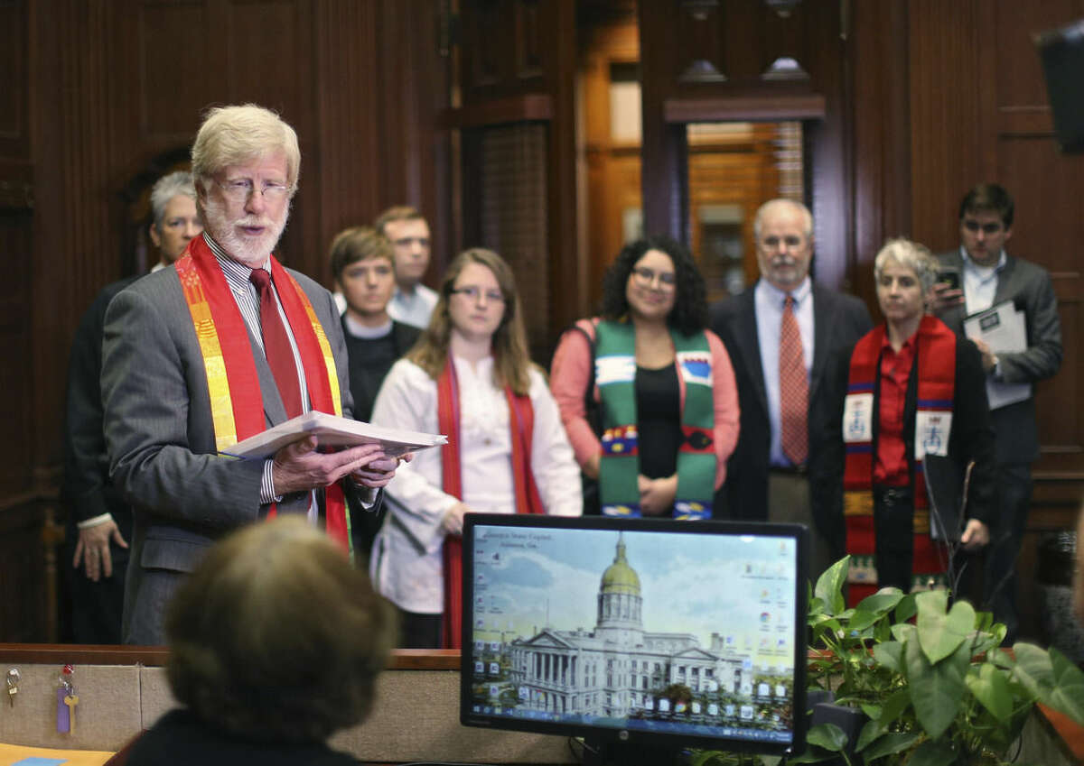 Gary Charles, center, head pastor of the Central Presbyterian Church, Gary Charles, left, head pastor of the Central Presbyterian Church, with other clergy behind him, delivers a letter to the office of Gov. Nathan Dea on Thursday, Nov. 19, 2015, as part of a national campaign targeting more than 20 governors who have said they want to close their borders to Syrians in the wake of the deadly attacks in Paris. In the letter they condemned proposals to discriminate against refugees on the basis of religion and supported the call to take in refugees. (Bob Andres/Atlanta Journal Constitution via AP)
