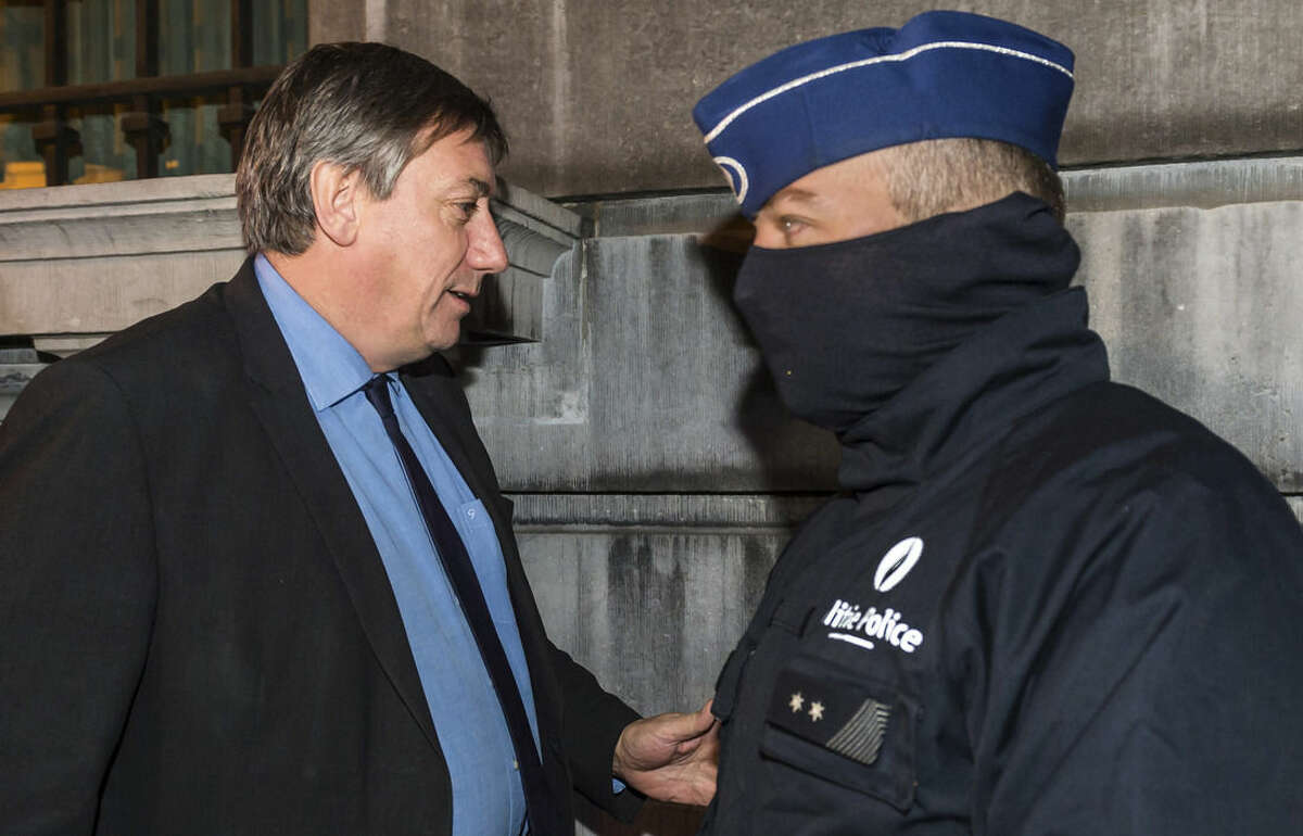 Belgium's Interior Minister Jan Jambon, left, walks by a police officer as he arrives to take part in a National Security Council meeting in Brussels on Sunday, Nov. 22, 2015. Western leaders stepped up the rhetoric against the Islamic State group on Sunday as residents of the Belgian capital awoke to largely empty streets and the city entered its second day under the highest threat level. With a menace of Paris-style attacks against Brussels and a missing suspect in the deadly Nov. 13 attacks in France last spotted crossing into Belgium, the city kept subways and underground trams closed for a second day. (AP Photo/Geert Vanden Wijngaert)