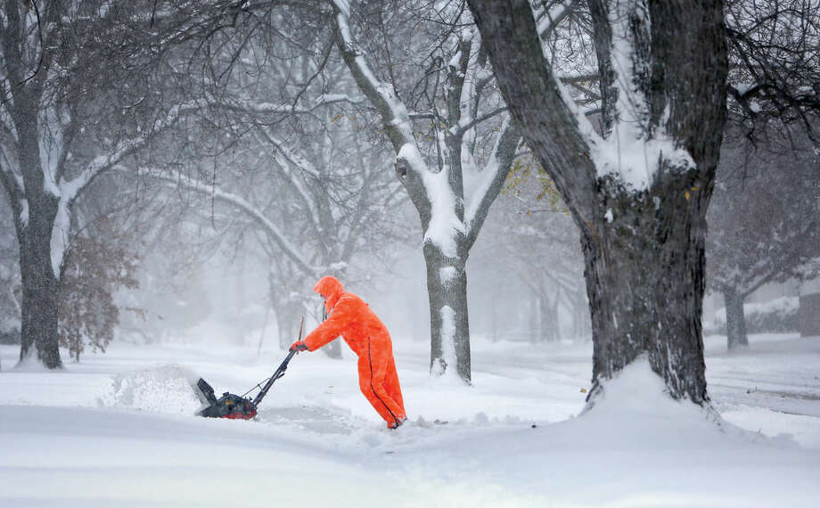 Gary Miller clears his neighbor's driveway after Friday's snowstorm in Janesville, Wis., on Saturday, Nov. 21, 2015. The first significant snowstorm of the season blanketed some parts of the Midwest with Janesville receiving several inches of snow. (Anthony Wahl/The Janesville Gazette via AP) MANDATORY CREDIT