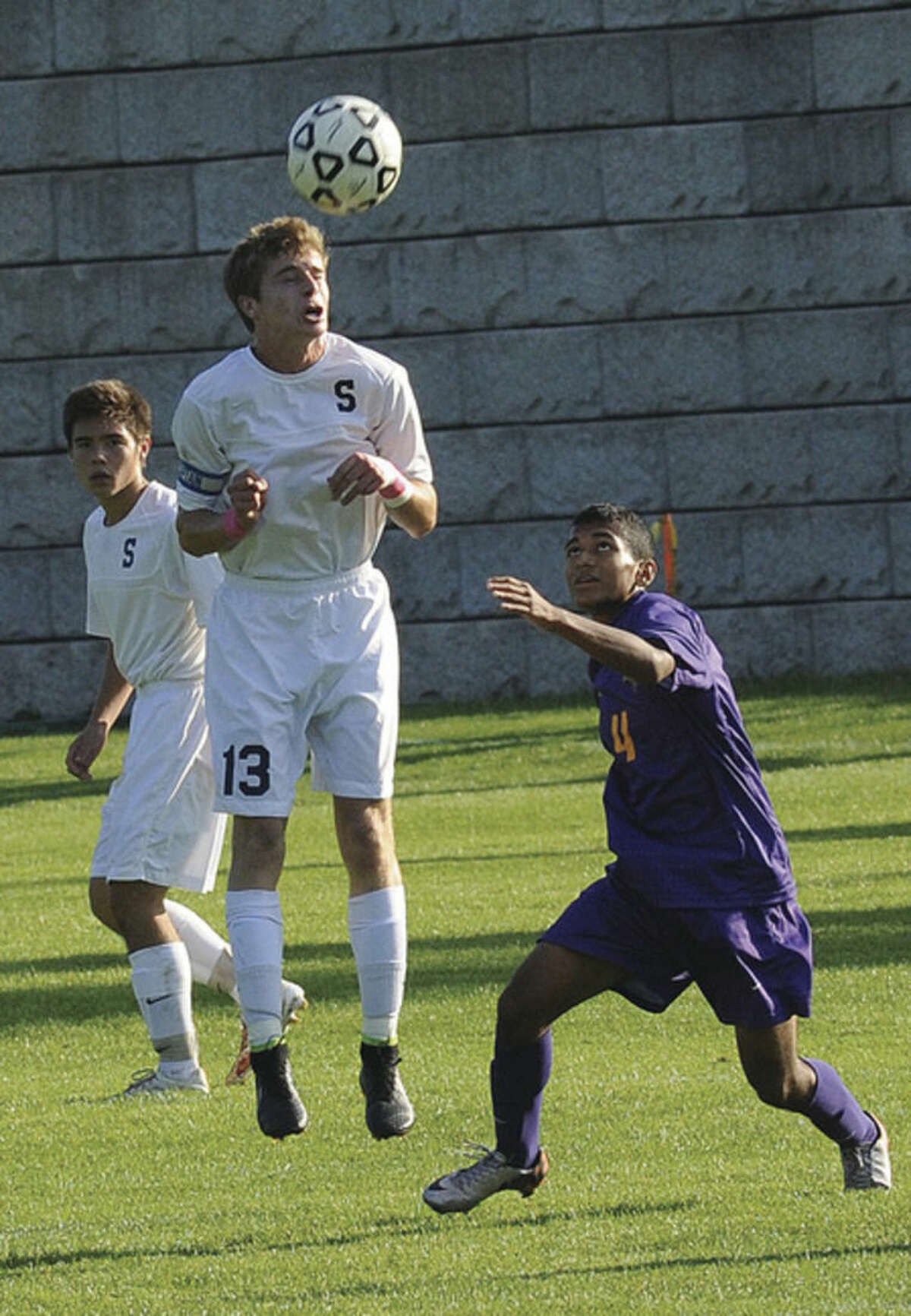 Hour photo/Matthew Vinci Staples Patrick Beusse jumps to head a ball over Westhill's Jose Vargas during Monday's game.
