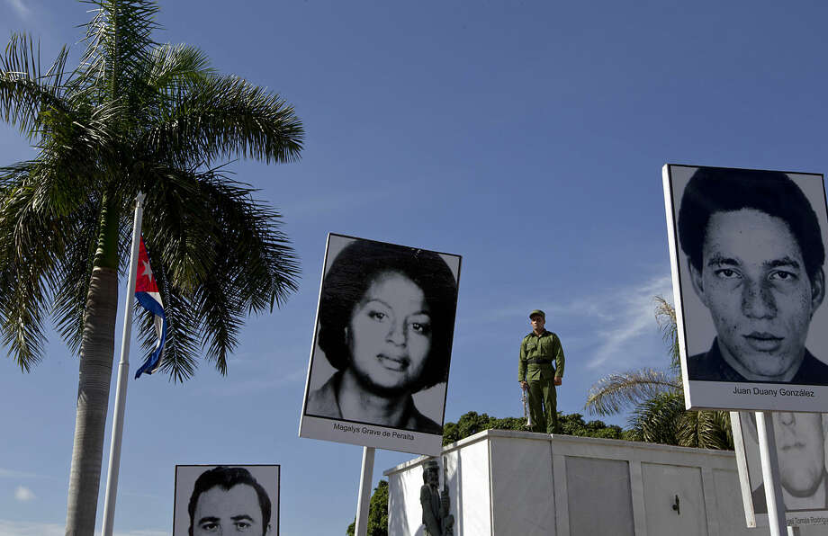 A trumpet player stands at attention, framed by placards that show the faces of people who died on Cubana Airline Flight 455, during a ceremony marking the 38th anniversary of the mid-air bombing, at the Colon Cemetery in Havana, Cuba, Monday, Oct. 6, 2014. The ceremony honored those who died in the Oct. 6, 1976 flight that killed 73 people. (AP Photo/Franklin Reyes)