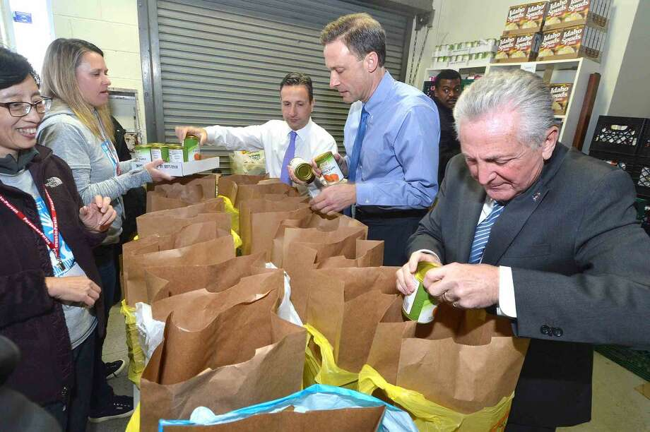 Hour Photo/Alex von Kleydorff Sen. Bob Duff , State Rep. Fred Wilms and Mayor Harry Rilling help FactSet volunteers to fill bags full of everything for Thanksgiving dinner at Person to Person
