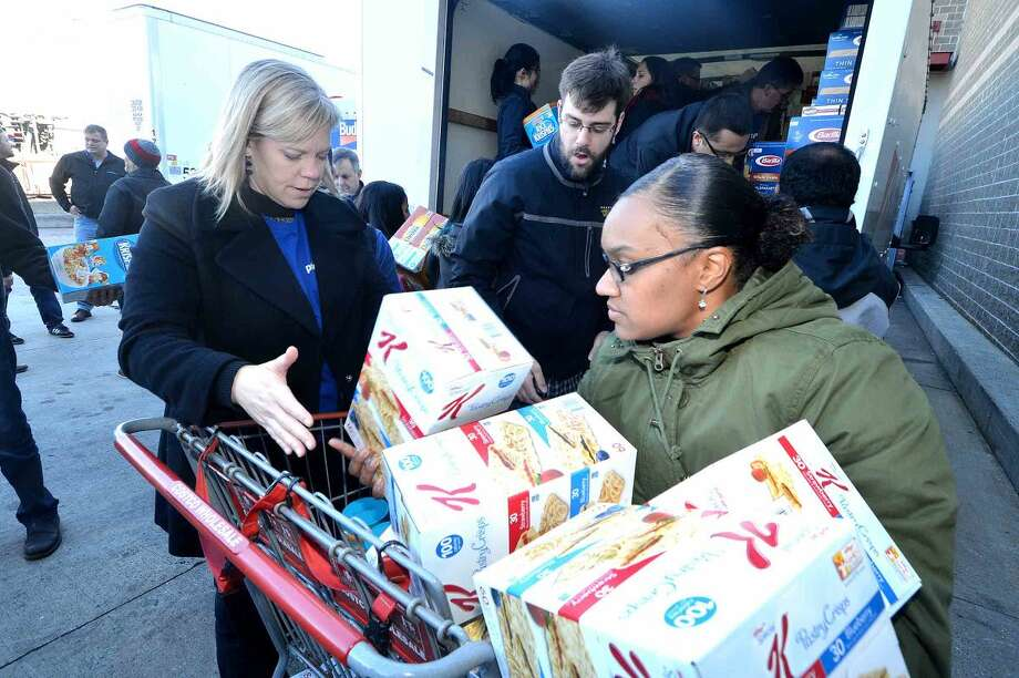 Hour Photo/Alex von Kleydorff Priceline employees Denise Bialek and Nyota Ferguson along with Carmine Iannaccone and others load trucks full of food purchased at Costco for distribution to local food banks