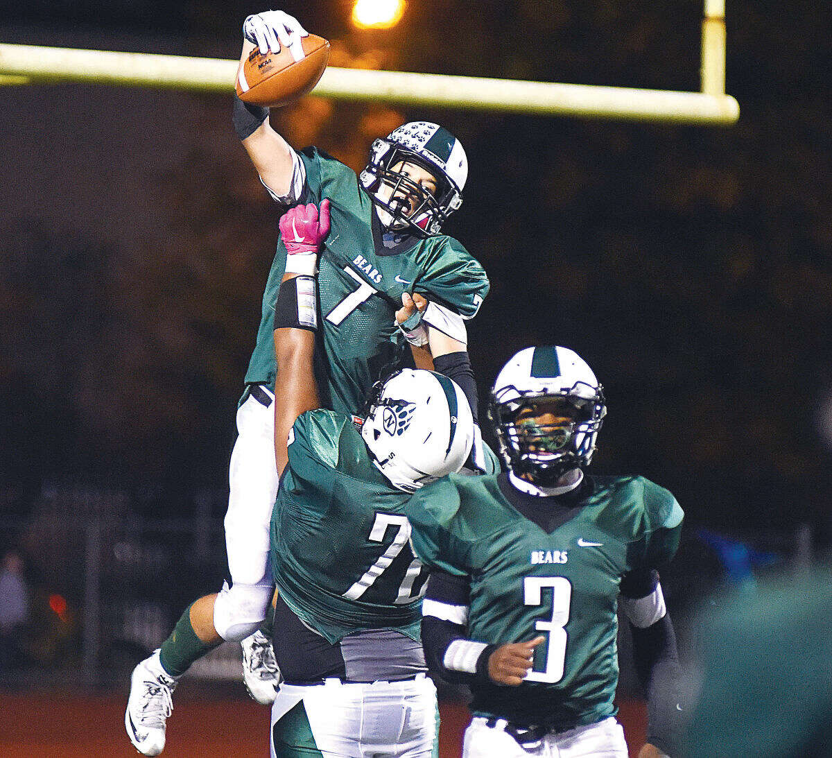 Hour photo/John Nash - Norwalk's Brendan Brown (7) gets hoisted into the air by teammate Luis Maturana as the Bears' Lester Harris jogs off the field during Friday night's 49-7 win over Bridgeport Central.