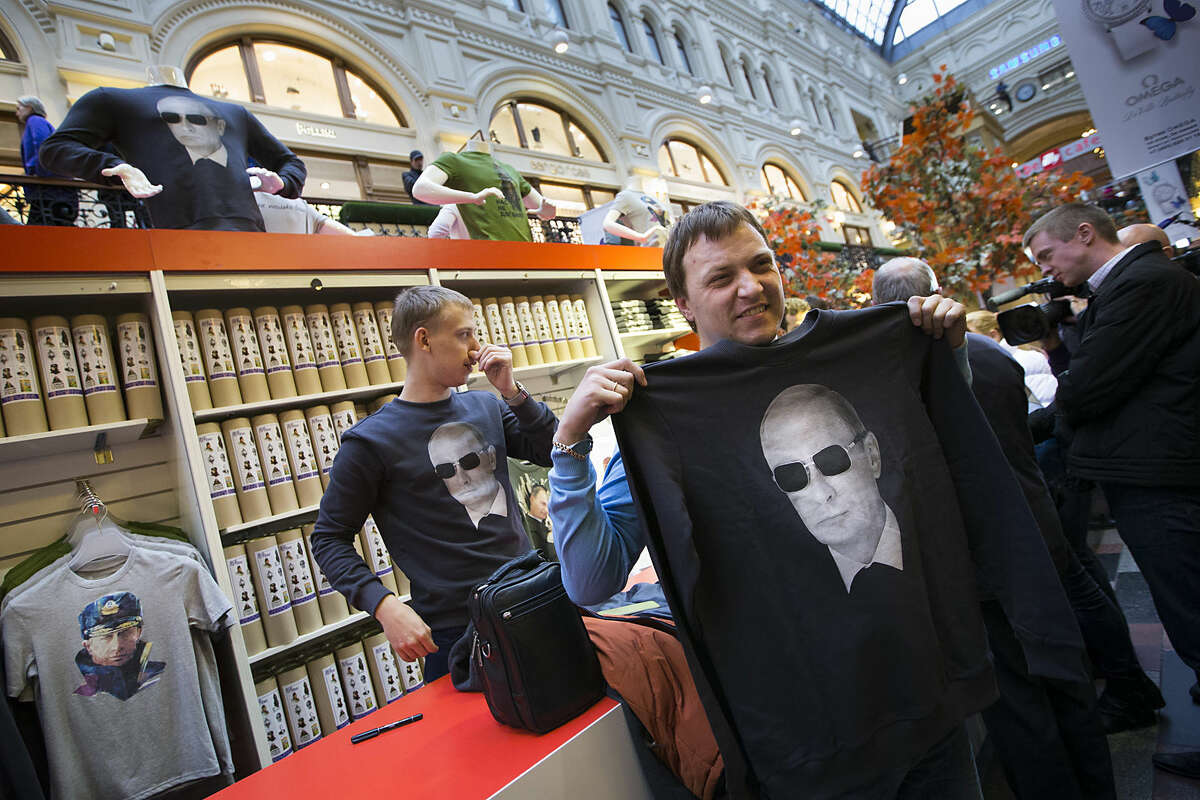 People choose shirts bearing an image of Russian President Vladimir Putin at GUM (the State Department Store) in Moscow, Russia, Monday, Oct. 6, 2014. Souvenirs and clothing featuring Putin or pro-government slogans have become popular in Russia this year. (AP Photo/Alexander Zemlianichenko)