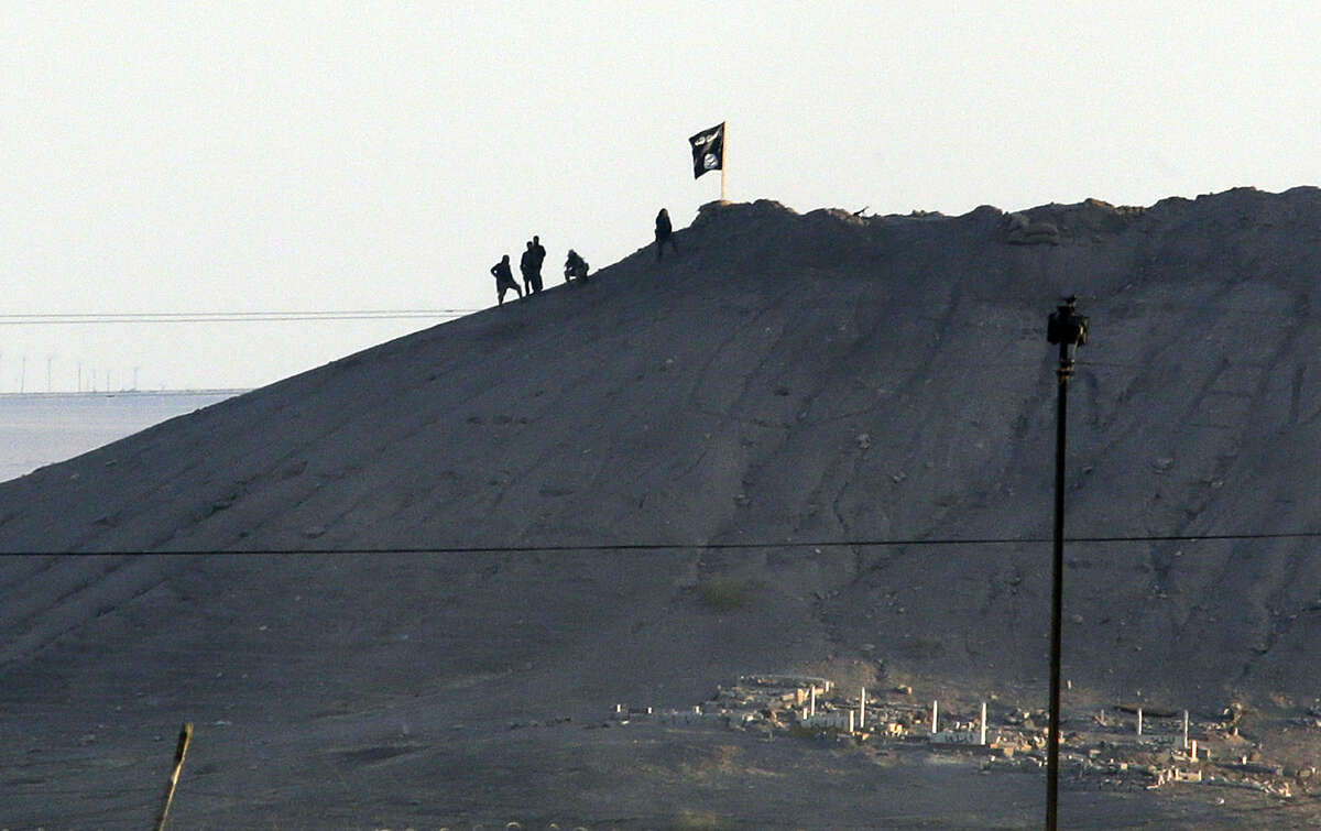 In this image shot with an extreme telephoto lens and through haze from the outskirts of Suruc at the Turkey-Syria border, militants with the Islamic State group are seen after placing their group's flag on a hilltop at the eastern side of the town of Kobani, Syria, where fighting had been intensified between Syrian Kurds and the militants of Islamic State group, Monday, Oct. 6, 2014. Kobani, also known as Ayn Arab and its surrounding areas have been under attack since mid-September, with militants capturing dozens of nearby Kurdish villages. The flag is indicating that the jihadists may have regrouped and broken through the Kurdish lines. (AP Photo/Lefteris Pitarakis)