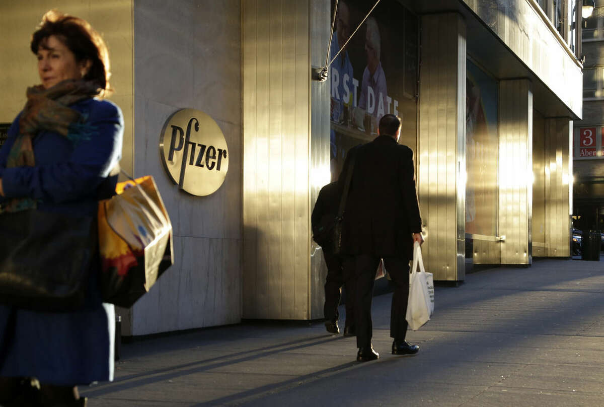 People pass Pfizer's world headquarters, Monday, Nov. 23, 2015, in New York. Pfizer and Allergan will join in a $160 billion deal to create the world's largest drugmaker. (AP Photo/Mark Lennihan)