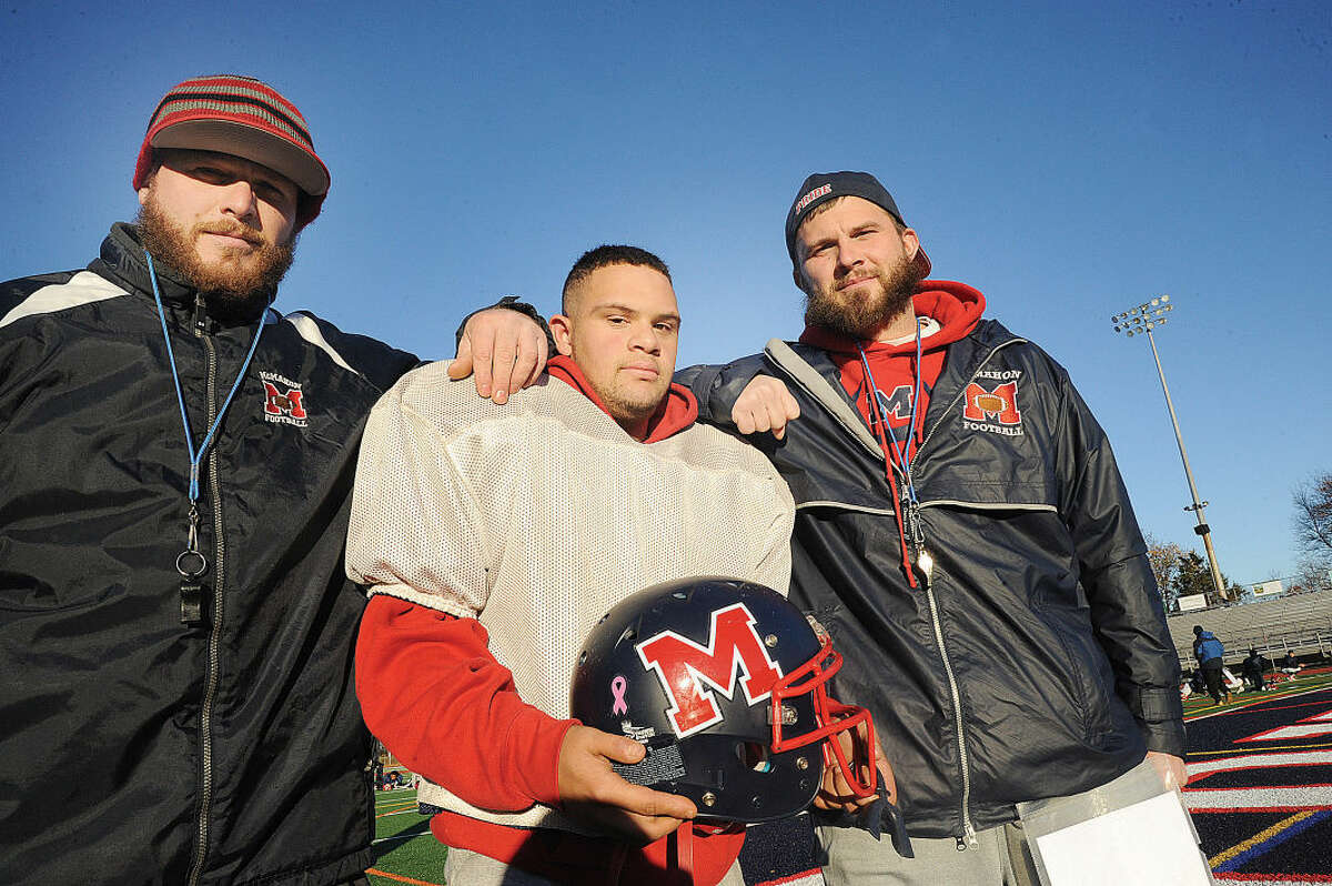 Brien McMahon junior Jamie Taylor with his cousins and coaches Joey Smith and Drew Smith. (Hour photo/Matthew Vinci)