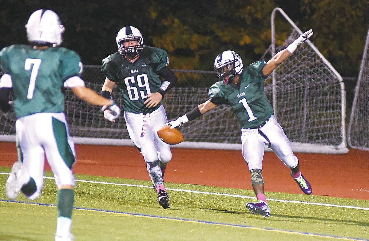 Hour photo/John Nash - Norwalk's Dakari Eason (1) soars through the end zone after scoring his first of two touchdowns as teammates Brendan Brown (7) and Eddie O'Hara (69) close in to celebrate.