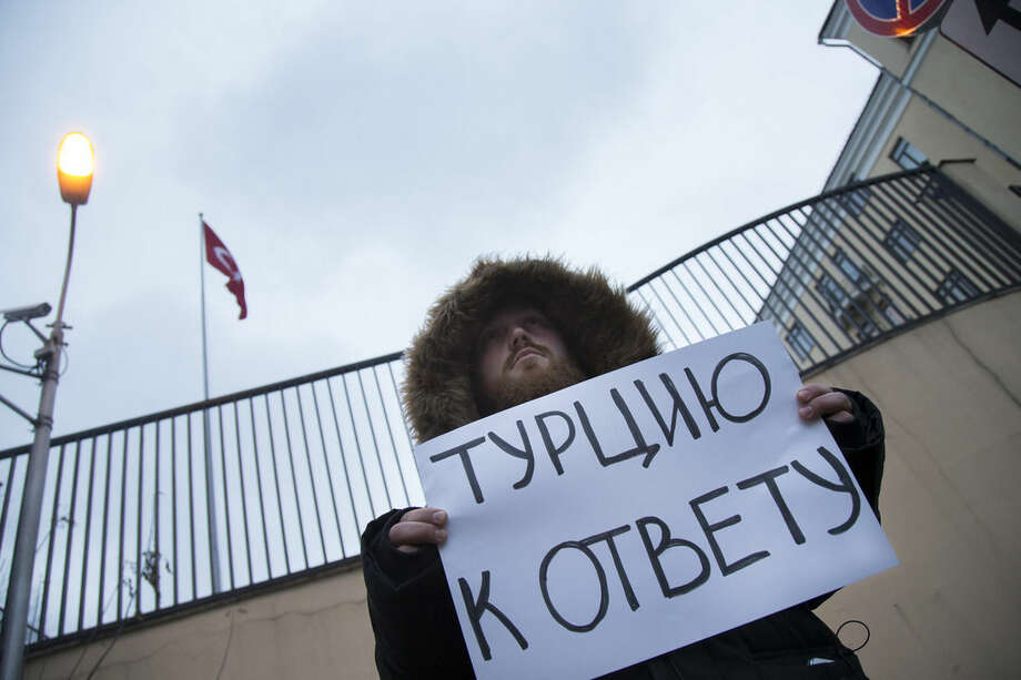 "A man holds a poster as he pickets the Turkish Embassy in Moscow, Russia, Tuesday, Nov. 24, 2015. Russian President Vladimir Putin on Tuesday has called Turkey's decision to down a Russian jet near the Syria border a ""stab in the back."" The poster reads : Turkey is responsible. (AP Photo/Alexander Zemlianichenko)"