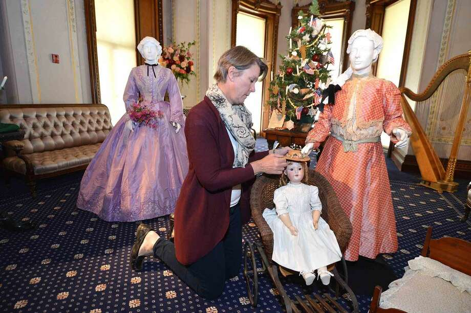 Hour Photo/Alex von Kleydorff Kathie Bennewitz works on setting a doll from the late 19th century in a toy stroller in one of the Vignette's for the new exhibit, Holiday Grandeur: The Mansion's toys and trains story at Lockwood Mathews Mansion Museum