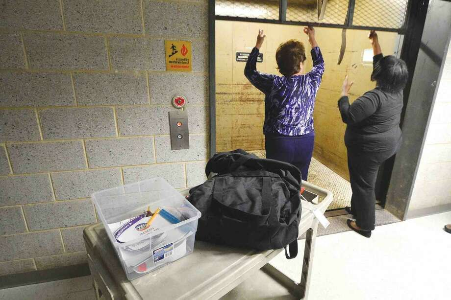 Hour Photo/Alex von Kleydorff Karen Doyle Lyons and Anissa Scovens lift the gate on the freight elevator to take the Ponus Ridge Middle school ballot's up in City Hall for a random picked recount