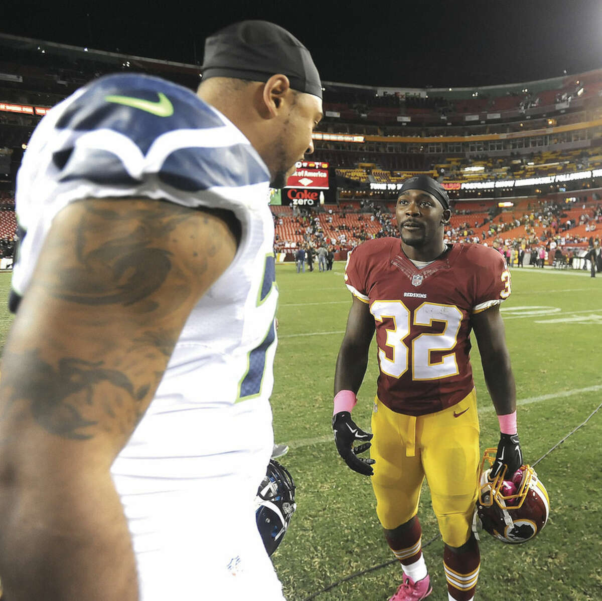 Hour photo/John Nash Norwalk's Silas Redd (32), a running back for the Washington Redskins, greets former Penn State teammate Garry Gilliam of the Seattle Seahawks after Monday night's NFL game at FedEx Field in Landover, Md.