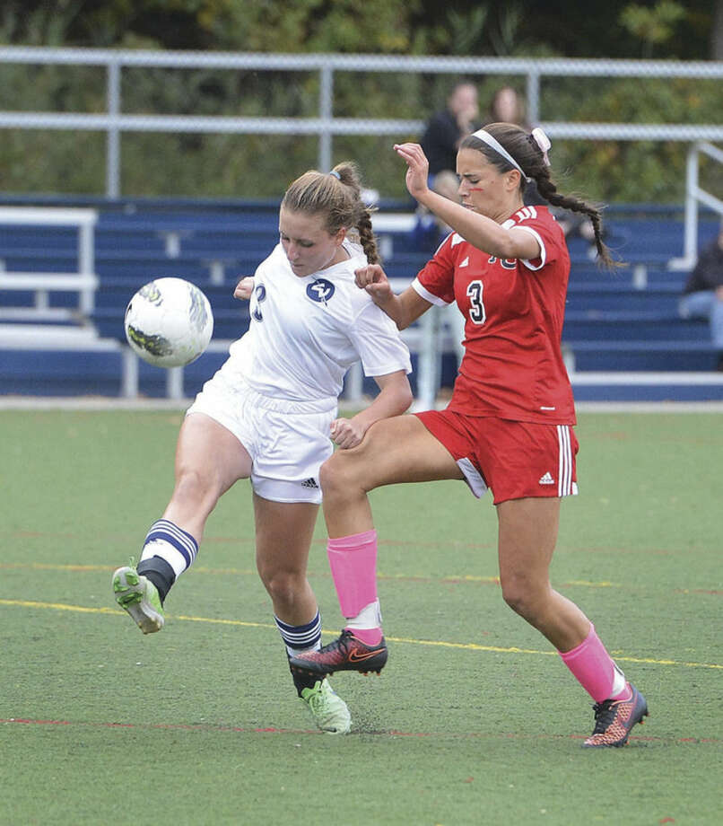 Hour photo/Alex von KleydorffWiltn's Paisley Eagan goes to pick a ball, while Elena Aliapoulios of New Canaan closes her down during Tuesday's game in Wilton.