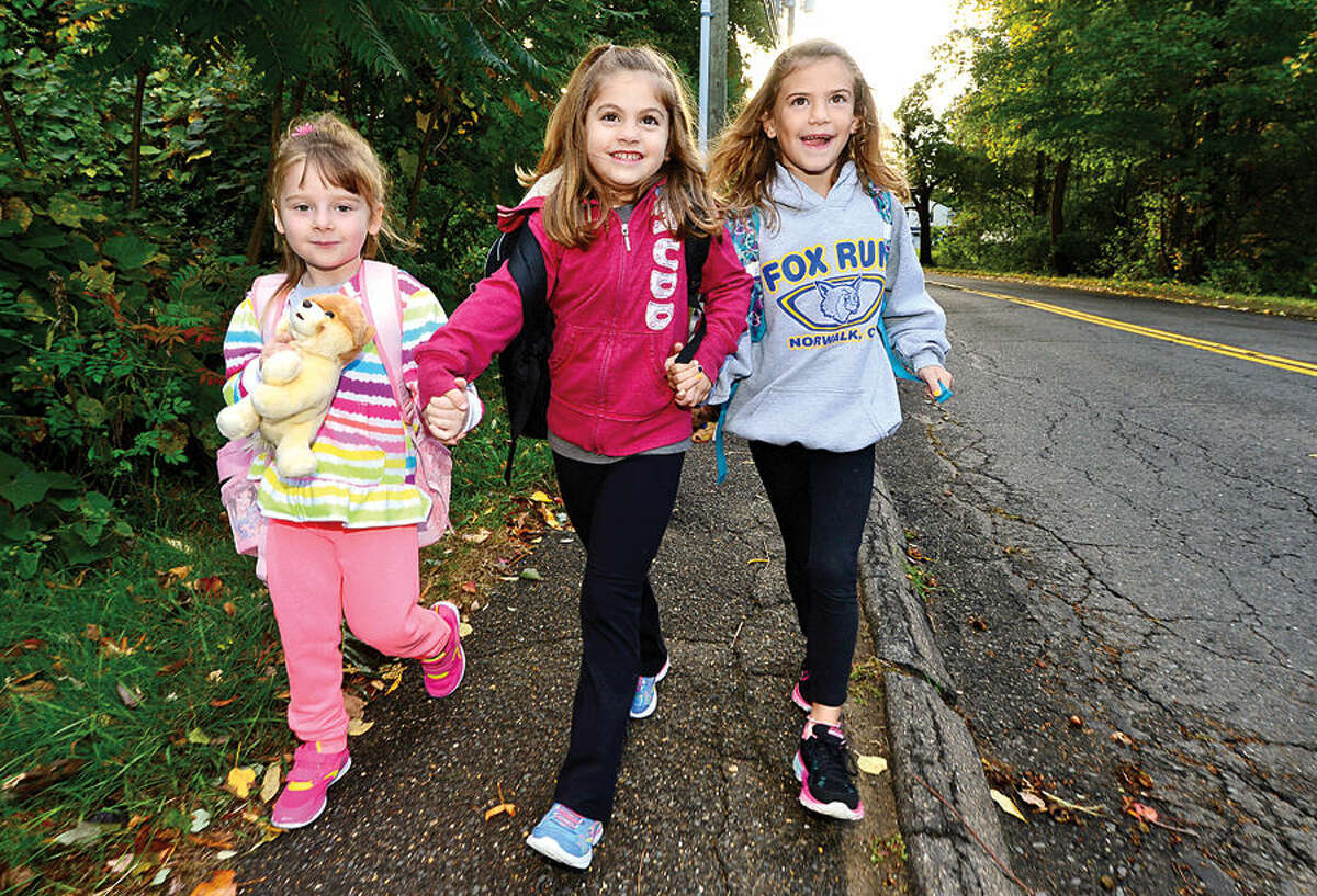 Hour photo / Erik Trautmann Fox Run Elementary School kindergartners Faith Ortolano and Jess Claps and first grader, Tory Hall, participate in their school's observance of International Walk to School Day in an effort to promote healthy lifestyles.