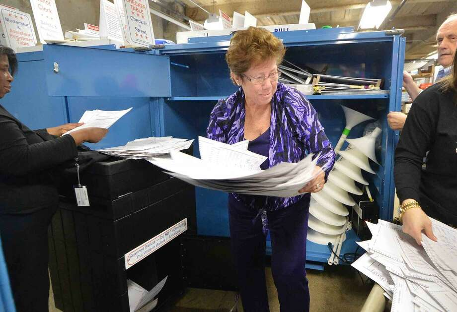 Hour Photo/Alex von Kleydorff Republican Registrar of Voters Karen Doyle Lyons grabs a stack of ballots from the Ballot Box that was used on election day at Ponus Ridge Middle School as part of Secretary of the State's Office random audit of Connecticut's Nov. 3 municipal election results.