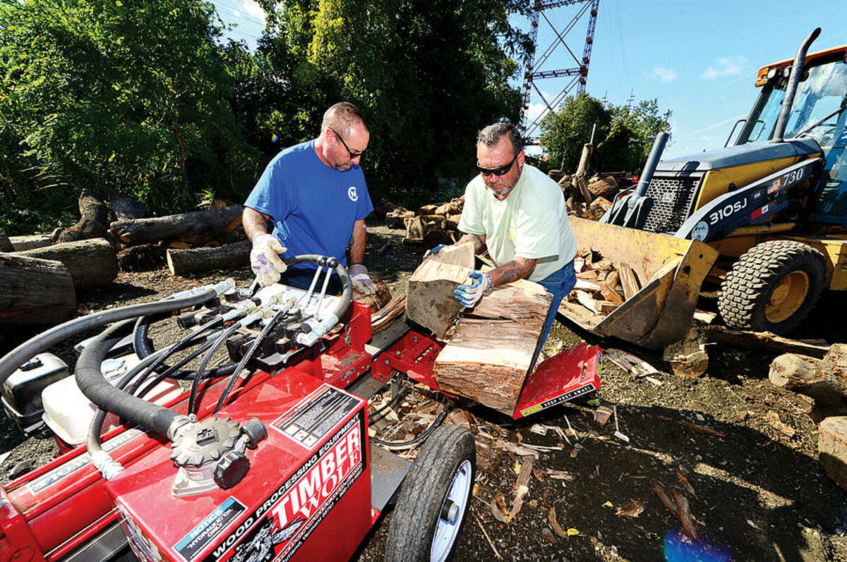 Hour photo / Erik Trautmann Norwalk REcreation and Parks workers Joe Conte and Duane Mewrritt slit wood for the City of Norwalk's new Resident Firewood Program. The first set of firewood vouchers had sold out online in 11 minutes on Monday morning. The inaugural sale netted $1125 in 11 minutes.