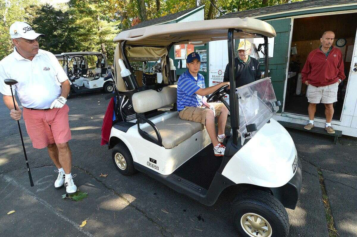 Hour Photo/Alex von Kleydorff Nathan Newhall and son Daniel grab a cart and head for the 1st hole at Oak Hills park on Wednesday