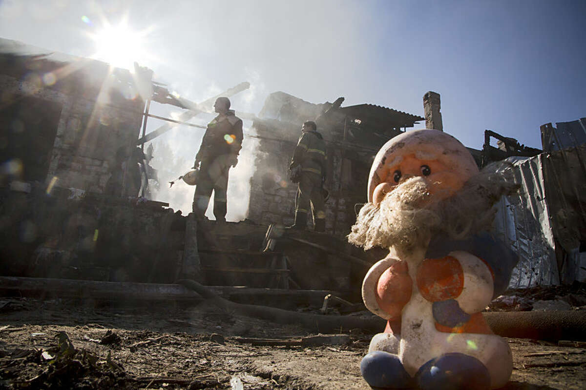 Firefighters inspect a burned house after shelling in the town of Donetsk, eastern Ukraine Friday, Oct. 10, 2014. (AP Photo/Dmitry Lovetsky)