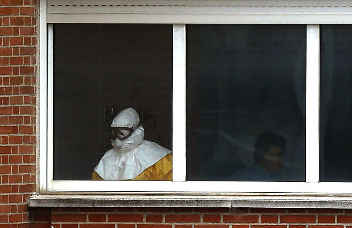 A medical practitioner wearing protective clothing stands next to an isolated patient on the sixth floor of the the Carlos III hospital in Madrid, Spain, Thursday, Oct. 9, 2014. Two doctors who treated a Spanish nurse who contracted Ebola have been admitted to a Madrid hospital for precautionary observation, bringing to six the number being monitored at the center. More than 50 other possible contacts were being monitored. The nurse, who had cared for a Spanish priest who died of Ebola, was the first case of Ebola being transmitted outside of West Africa, where a months-long outbreak has killed at least 3,500 people and infected at least twice as many. (AP Photo)