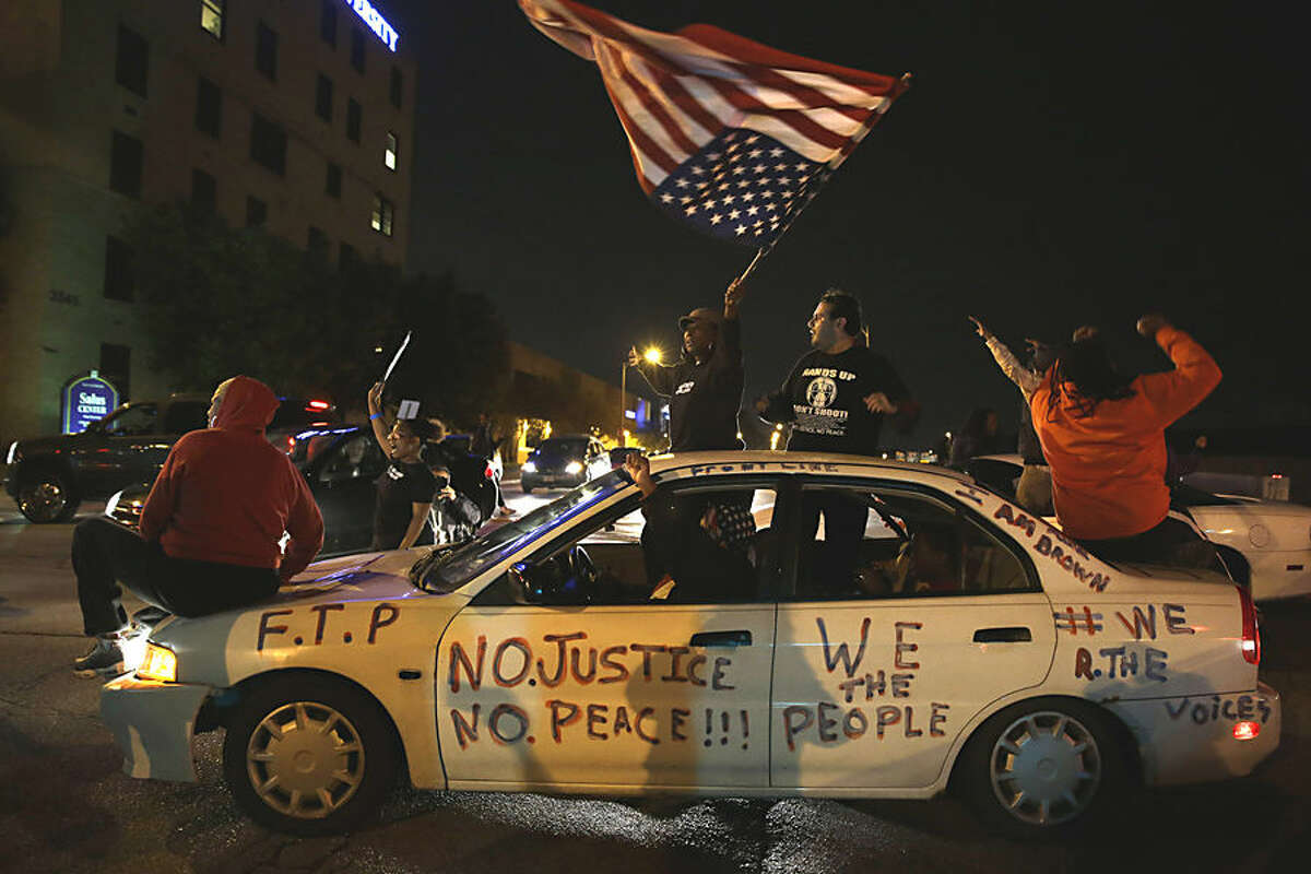 Protesters block a street Thursday, Oct. 9, 2014, a day after Vonderrit D. Myers was shot and killed by white, off-duty St. Louis police officer in St. Louis. Police say Myers was shot Wednesday after he opened fire on the off-duty officer, but Myers' parents say he was unarmed.(AP Photo/Jeff Roberson)
