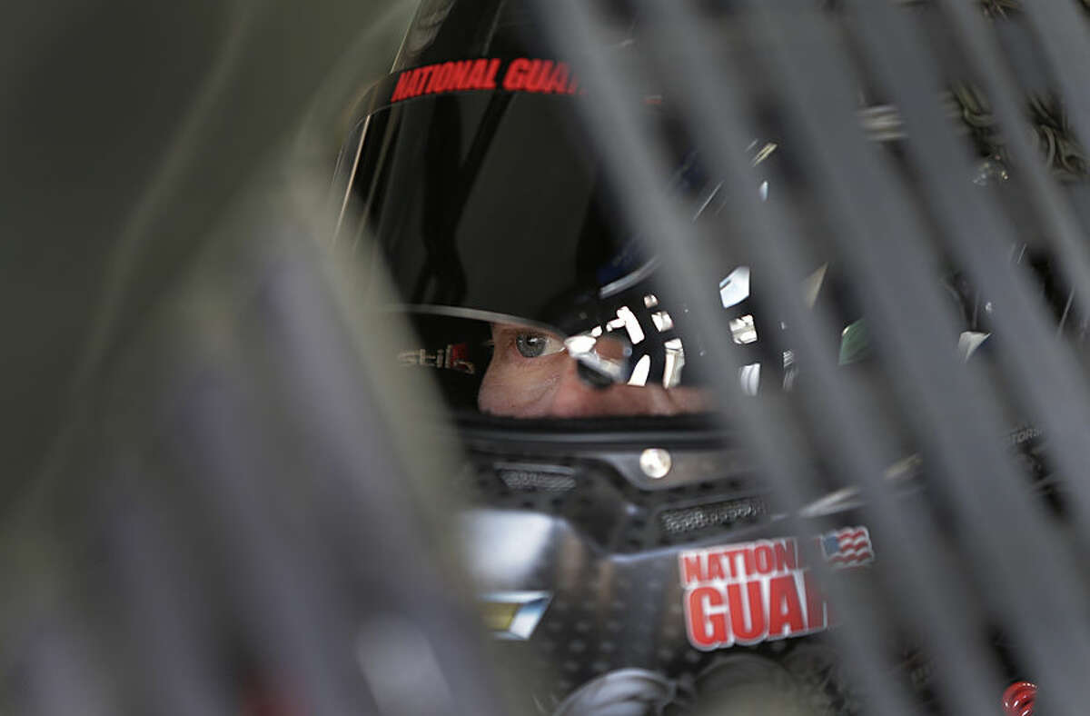 Dale Earnhardt Jr. looks from his car before practice for Saturday's NASCAR Bank of America Sprint Cup series auto race in Concord, N.C., Thursday, Oct. 9, 2014. (AP Photo/Chuck Burton)