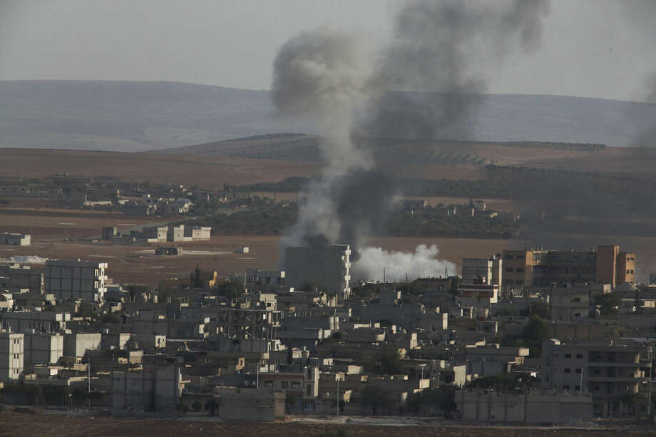 Smoke rises following an airstrike by US-led coalition aircraft in Kobani, Syria, during fighting between Syrian Kurds and the militants of Islamic State group, Thursday, Oct. 9, 2014. Kobani, also known as Ayn Arab, and its surrounding areas, has been under assault by extremists of the Islamic State group since mid-September and is being defended by Kurdish fighters. (AP Photo/Lefteris Pitarakis)
