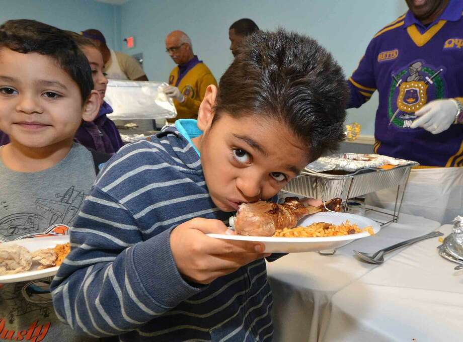 Hour Photo/Alex von Kleydorff 8yr old Bryan Flores cant wait to get to his turkey leg and starts eating while in line with his family during the Community Thanksgiving Dinner sponsored by Ernie and Martha Dumas and South Norwalk residents