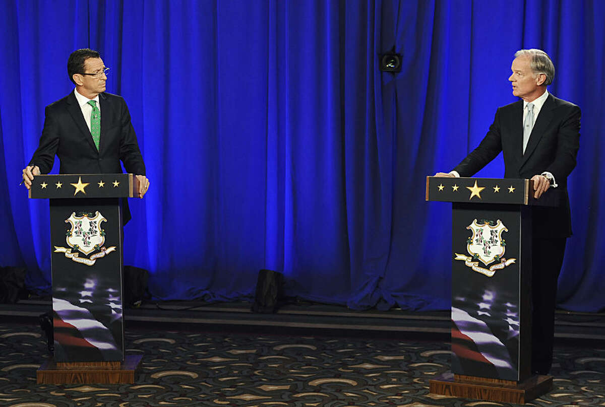 Incumbent Democrat Gov. Dannel P. Malloy, left, and Republican candidate for governor Tom Foley look at one another during an exchange about gun laws during a debate Thursday, Oct. 9, 2014, in Hartford, Conn. (AP Photo/Jessica Hill)