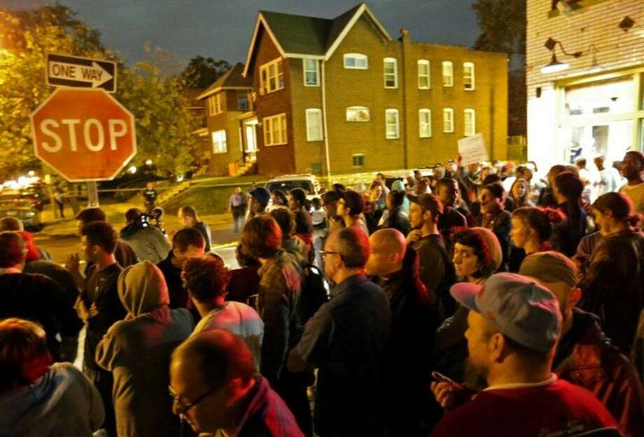 A crowd gathers near the scene in the 4100 block of Shaw Boulevard where a man was fatally shot by an off-duty St. Louis police officer on Wednesday, Oct. 8, 2014. St. Louis Police Lt. Col. Alfred Adkins said the 32-year-old officer was working a secondary security job late Wednesday when the shooting happened. (AP Photo/St. Louis Post-Dispatch, David Carson)