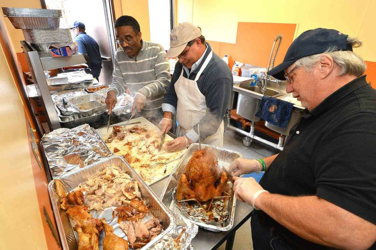Hour Photo/Alex von Kleydorff Bruce Morris, Andy Garfunkel and Rick McQuaid carve up turkys from the fryer during the Community Thanksgiving Dinner sponsored by Ernie and Martha Dumas and South Norwalk residents