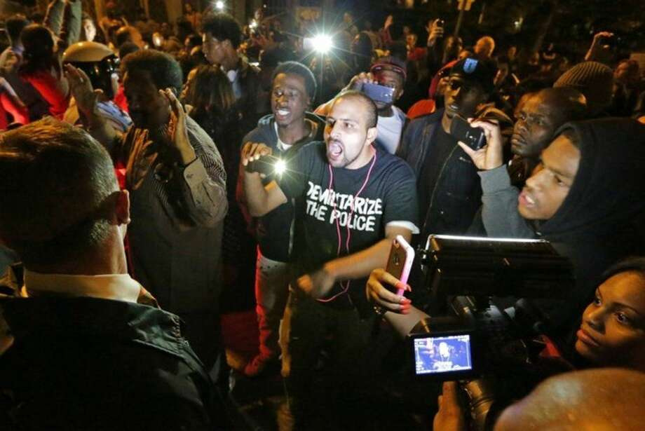 Crowds confront police near the scene in in south St. Louis where a man was fatally shot by an off-duty St. Louis police officer on Wednesday, Oct. 8, 2014. St. Louis Police Lt. Col. Alfred Adkins said the 32-year-old officer was working a secondary security job late Wednesday when the shooting happened. (AP Photo/St. Louis Post-Dispatch, David Carson)