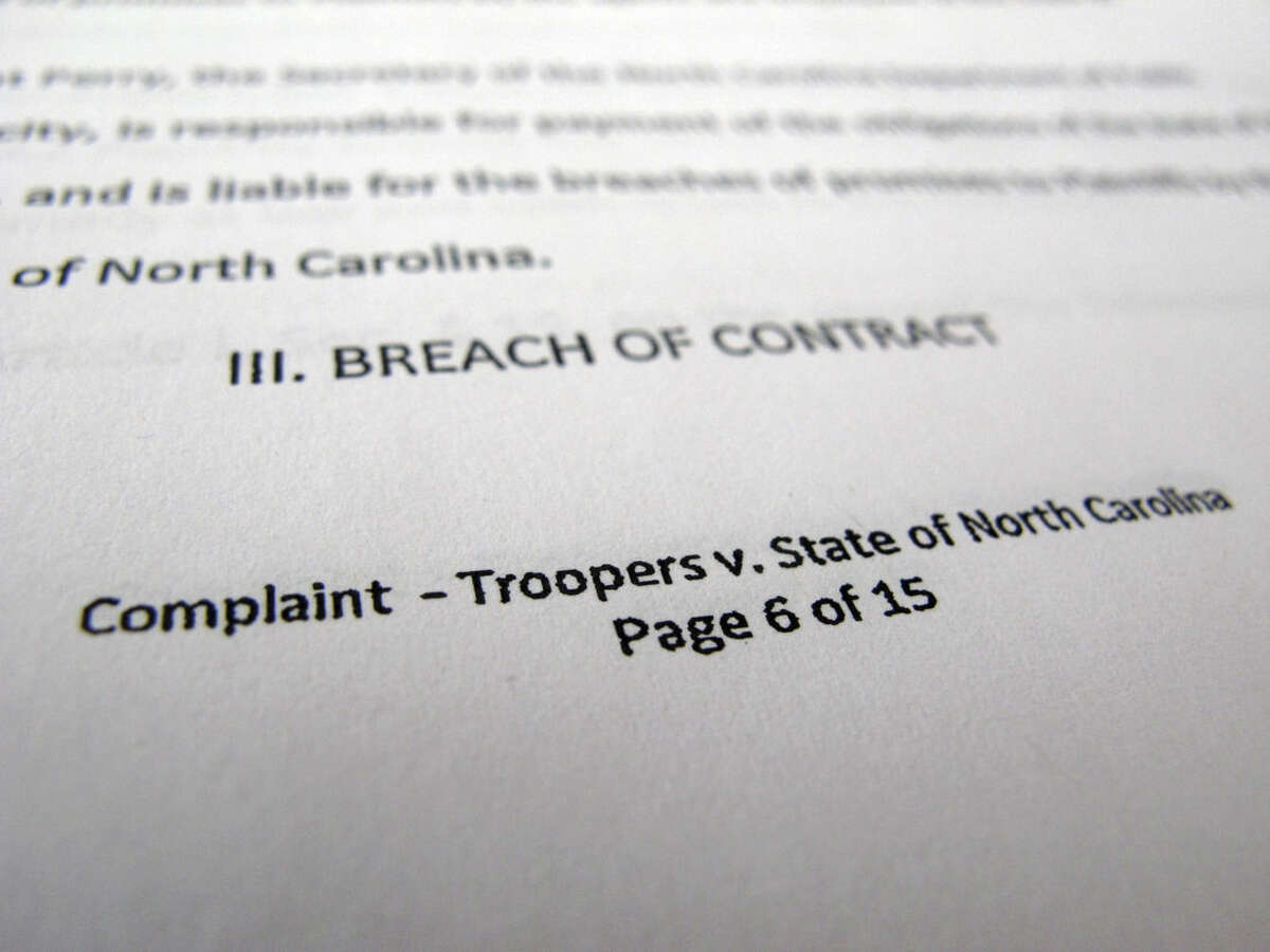 This photo taken Nov. 18, 2015 shows a close-up of a lawsuit filed by North Carolina state troopers who argue that the state reneged on pay raises that were promised to them when they were hired. Troopers say the situation has caused them financial hardship, forcing some to work second jobs and others to accept food stamps or other government assistance. (AP Photo/Allen G. Breed)